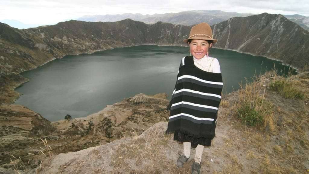 smiling young indigenous girl in poncho at quilotoa lagoon ecuador