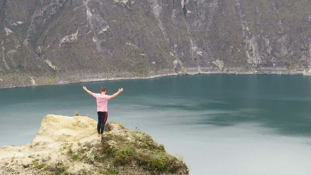 a tourist with outstretched arms with spectacular quilotoa lagoon in the background