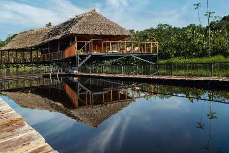 Main building at Sacha Lodge reflecting in the clear jungle waters in ecuador's amazon