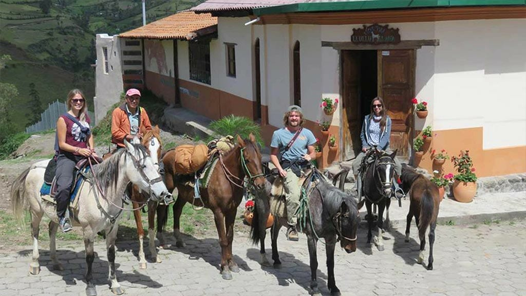 group of tourists horse riding at llullu llama hostal isinlivi ecuador