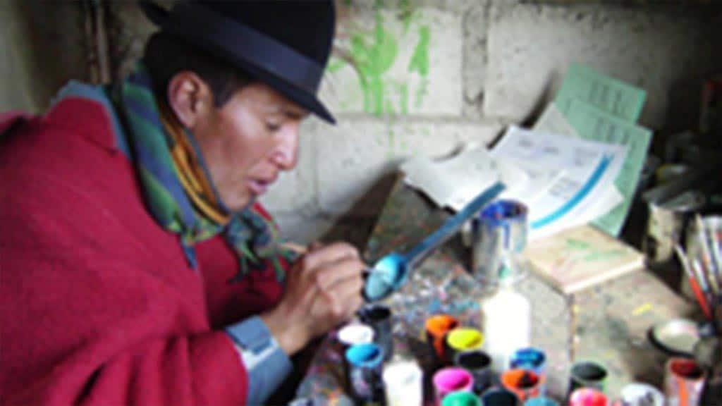 local artist painting a spoon at quilotoa ecuador