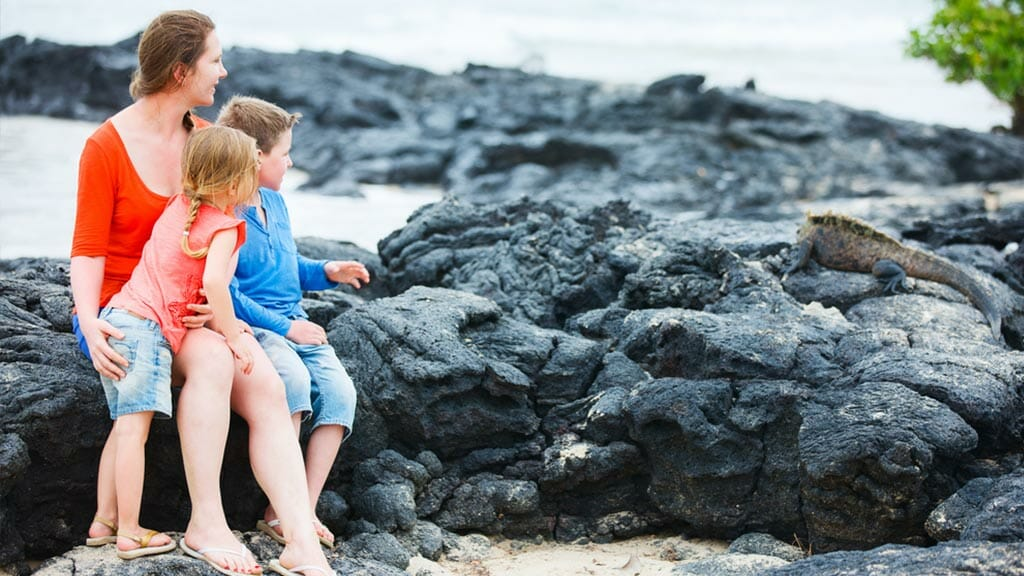 Mother and two kids at Galapagos watching a marine iguana on the rocks
