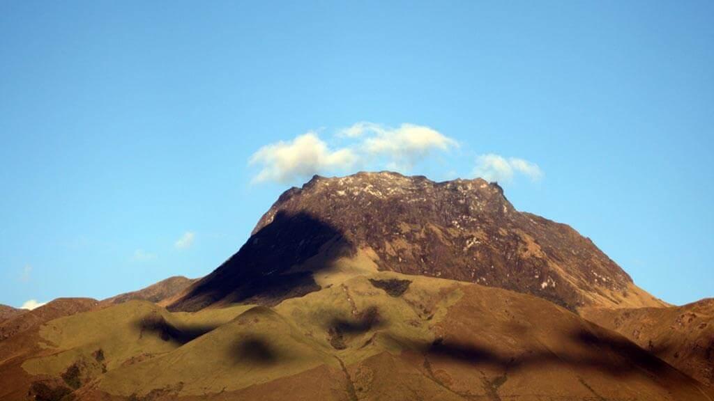 ecuador's imbabura volcano peak with blue sky and green slopes
