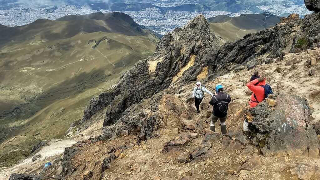 trek down from pichincha volcano with quito city below