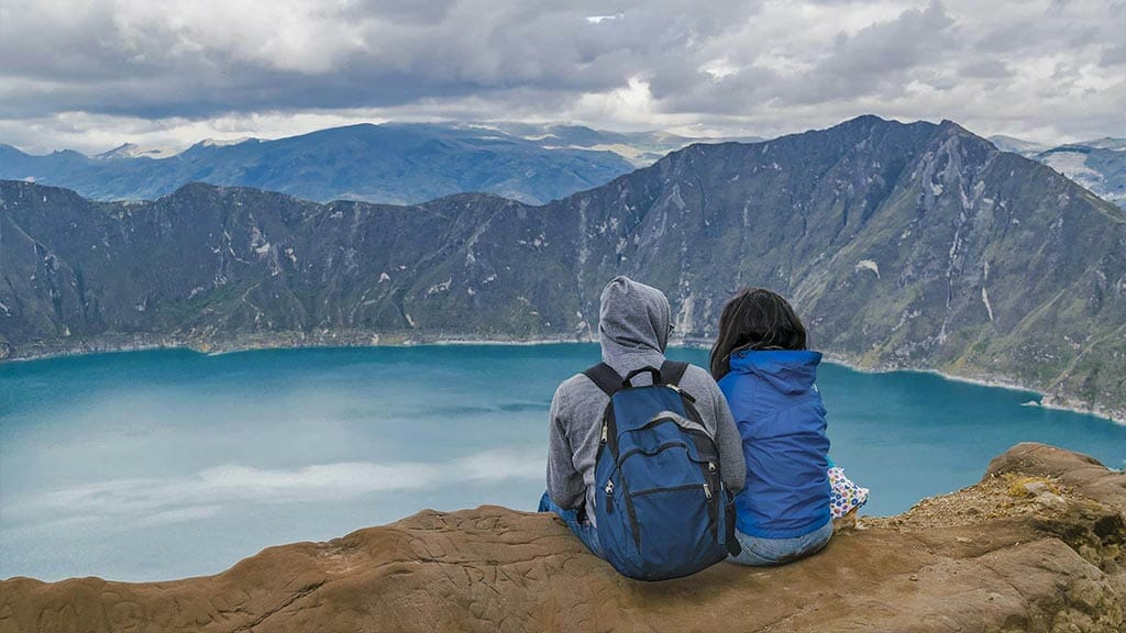 two tourists sit admiring the amazing view of quilotoa crater lake in ecuador