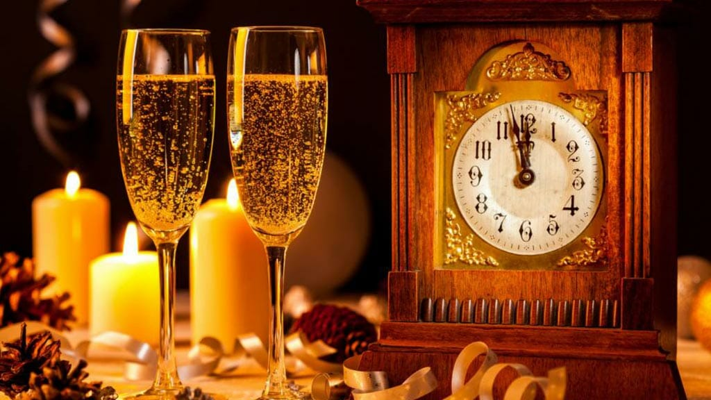 two glasses of champagne ready to celebrate new years when the clock strikes twelve
