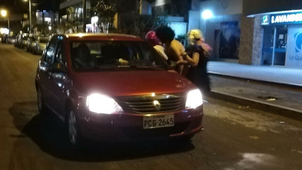 ecuador new year tradtions - men in drag collect taxes from a passing car