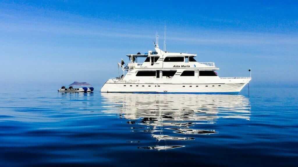 Galapagos cruise - Aida Maria yacht anchored at the Galapagos islands with panga boat behind