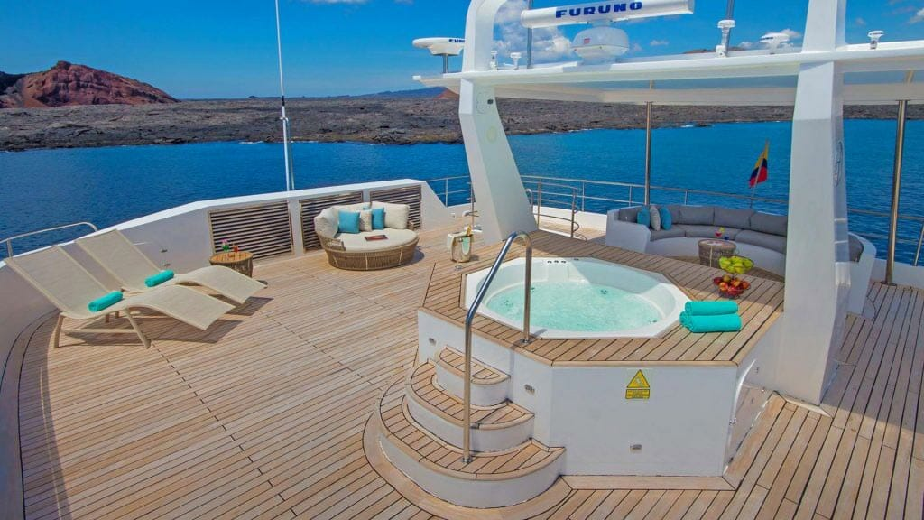 Alya catamaran Galapagos cruise - large wooden decked sun deck with loungers and jacuzzi