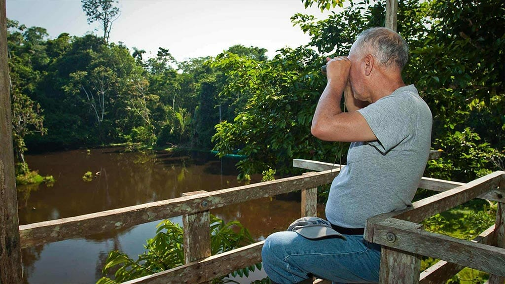 a tourist looks out with binoculars over a dark water rainforest lake at amazon dolphin lodge ecuador