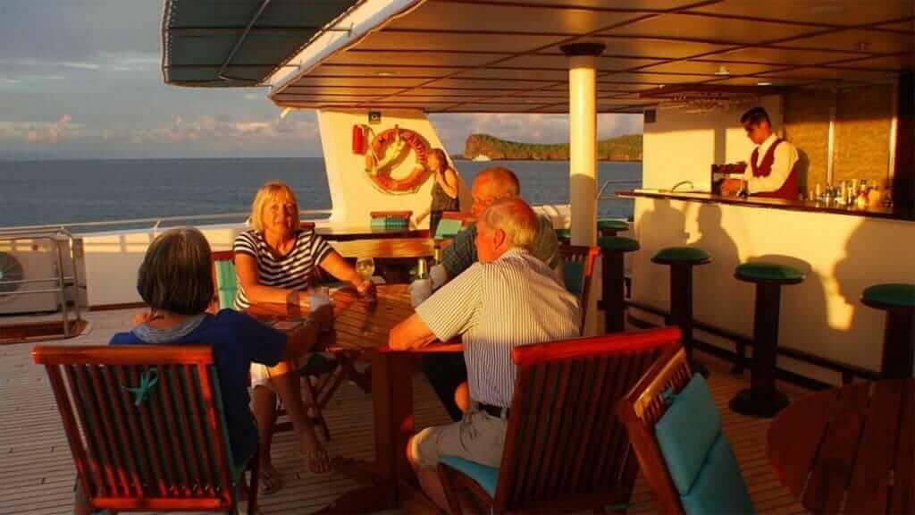Anahi Catamaran yacht Galapagos cruise - tourists enjoy a drink at the al fresco bar area