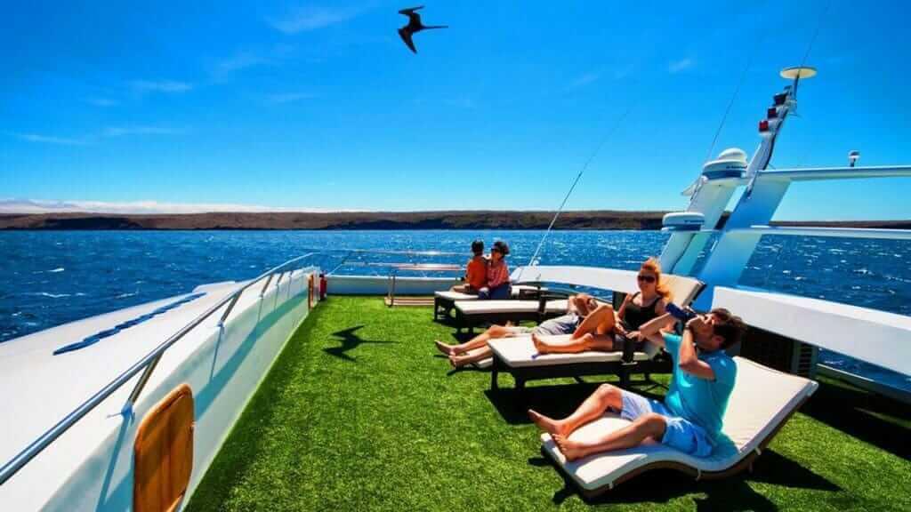 Anahi Catamaran yacht Galapagos cruise - sun deck with loungers and tourists watching frigate bird overhead