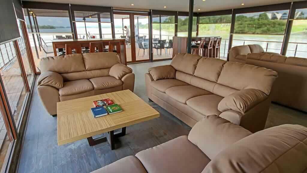anakonda river cruise ecuador - comfortable lounge with sofas and amazon rainforest views