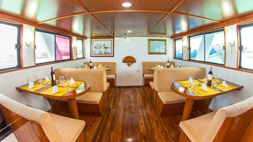 Aqua yacht Galapagos cruise - indoor dining area with 4 tables