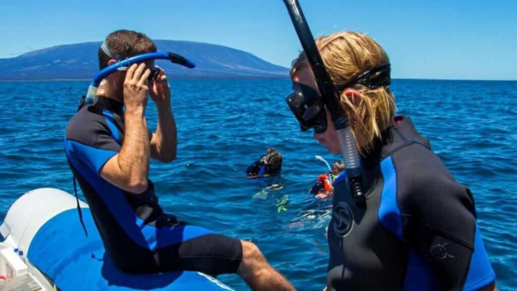 Archipel 1 yacht Galapagos cruise - tourists snorkeling from panga boat