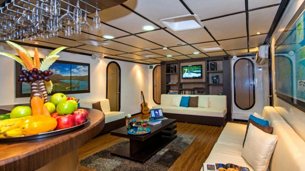 Archipel I yacht Galapagos cruise - indoor lounge with fruit and guitar