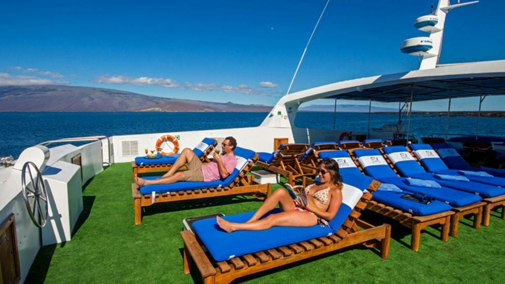 Archipel 1 yacht Galapagos cruise - tourists enjoy the sundeck with comfy loungers