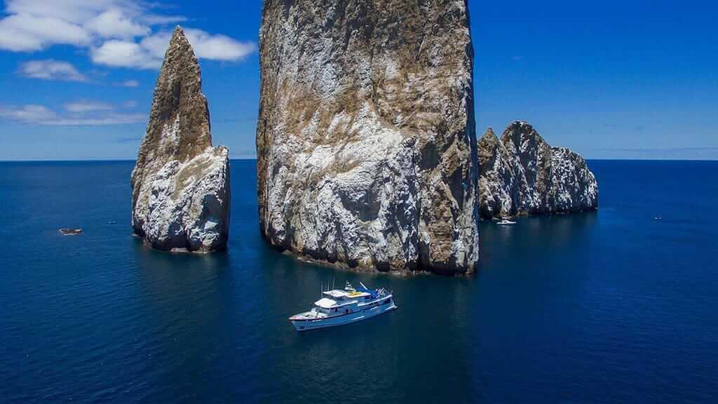 Beluga yacht Galapagos cruise - stunning aerial photo of the Beluga in fron of towering rocks and blue ocean
