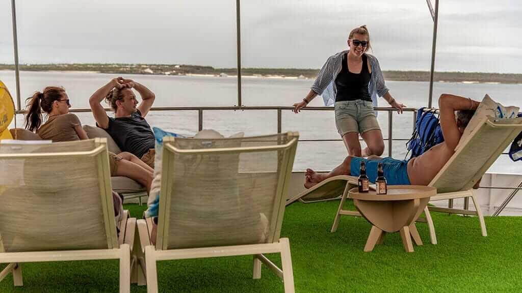bonita yacht galapagos islands cruise - tourists relaxing on sundeck