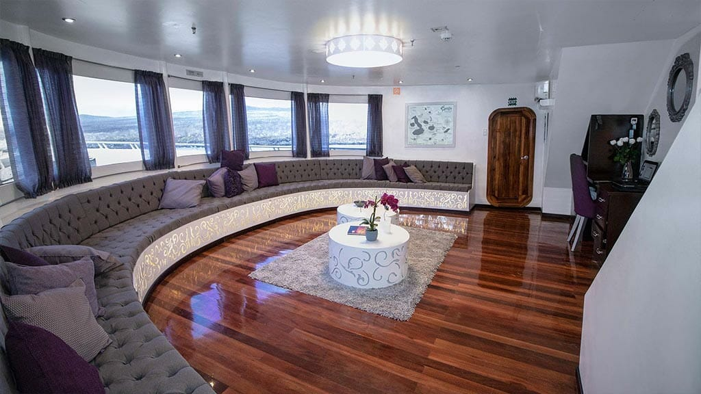 Camila yacht Galapagos cruise - social lounge area with semi-circle sofa and tv