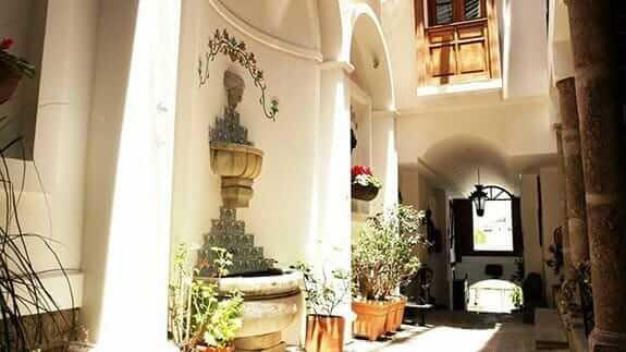 casa san marcos hotel quito ecuador - hallway with water fountain