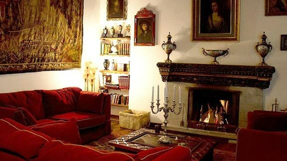 open fireplace, cosy sofa and wall hanging at hotel casa san marcos in quito