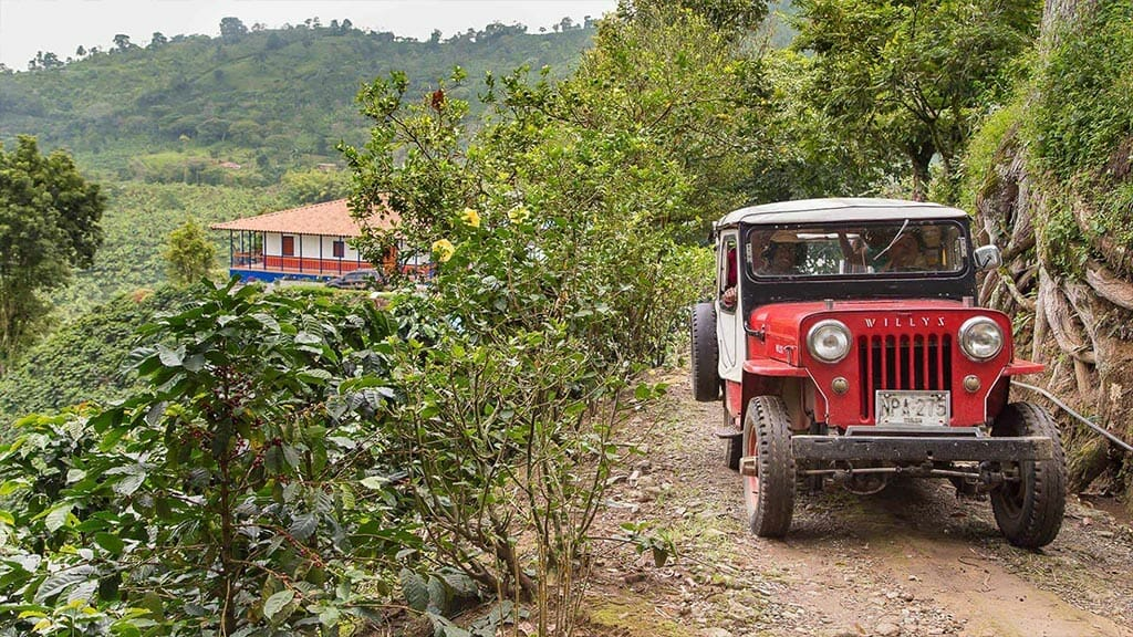 red jeep driving through lush green hills of colombia coffee region
