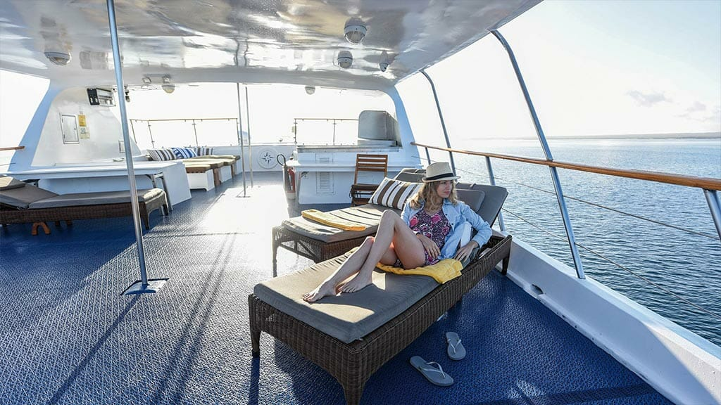 coral 1 and 2 yachts galapagos cruises - a tourist enjoying the ocean views from her shaded sun lounger