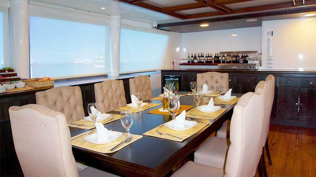 cormorant catamaran yacht galapagos island cruise - dining table and bar area