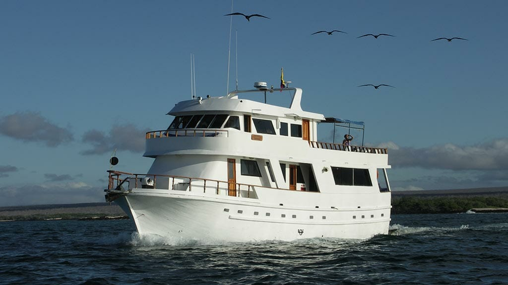 Darwin yacht galapagos cruise - side view of the Darwin yacht with frigate birds flying overhead