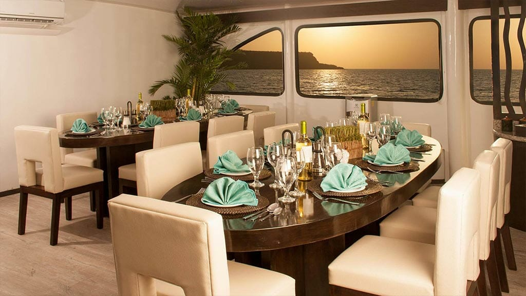 ecogalaxy II catamaran galapagos cruise - dining tables with sunset view through window