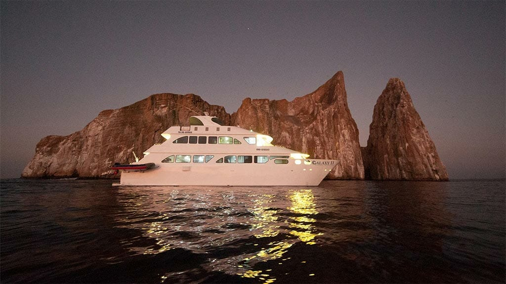 ecogalaxy II catamaran galapagos cruise - Galaxy 2 yacht illuminated at night in front of Kicker Rock