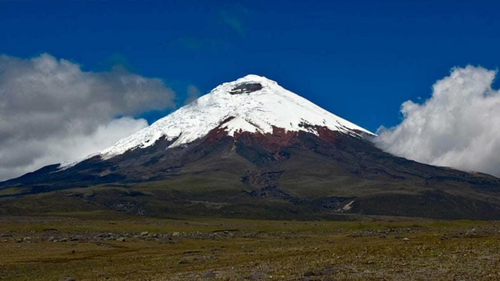 impressive view of snow capped cotopaxi volcano with blue sky in ecuador