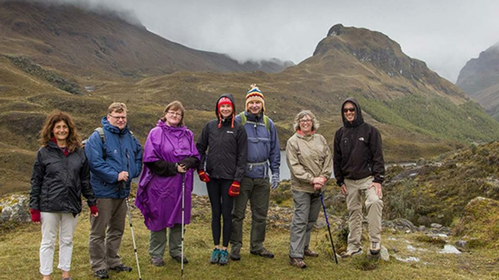 group of cold tourists pose with el cajas ecuador scenery