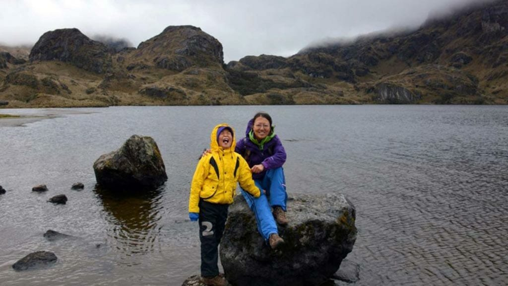 two tourists sitting on rock at el cajas national park ecuador