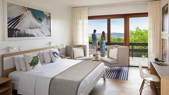 tourists enjoy views from their balcony at finch bay hotel galapagos