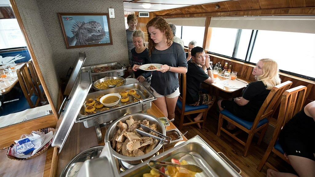 Fragata yacht cruise Galapagos Island - tourists serving dinner buffet