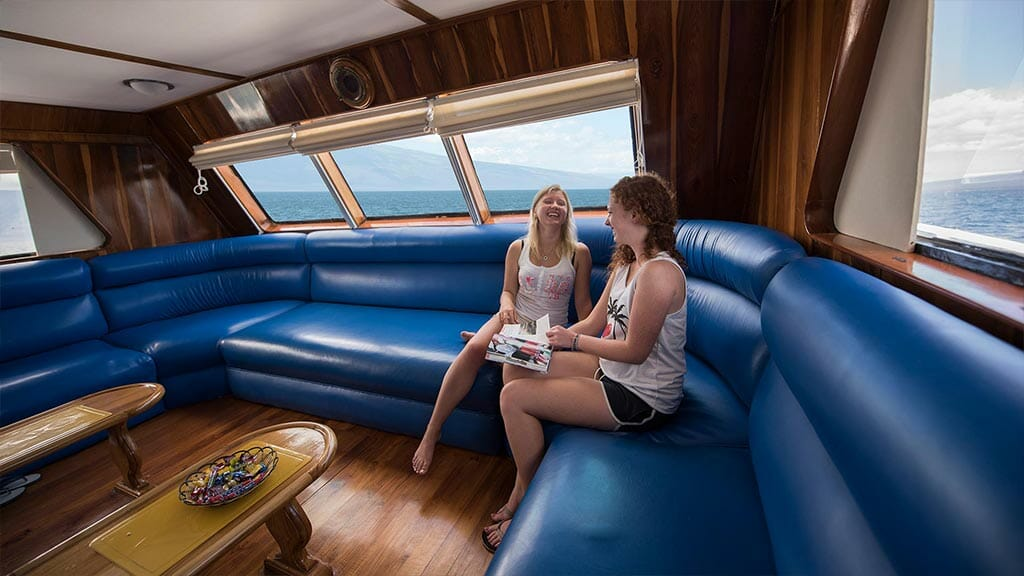Fragata yacht cruise Galapagos Island - tourists reading a magazine in the lounge area