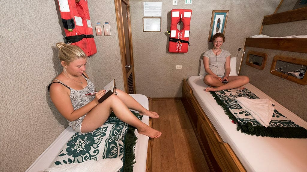 Fragata yacht cruise Galapagos Island - two tourists relaxing in their twin bed cabin
