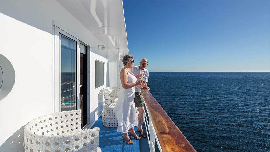 Legend cruise ship Galapagos Islands - tourist couple enjoy the sea views from their private balcony