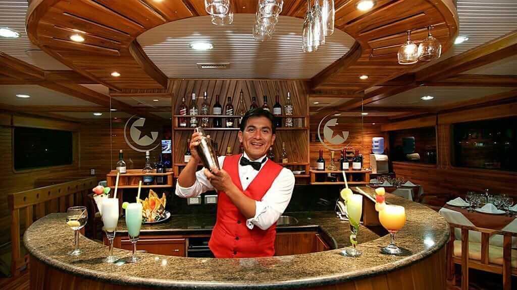 Galaxy yacht Galapagos cruise - barman prepares a range of cocktails