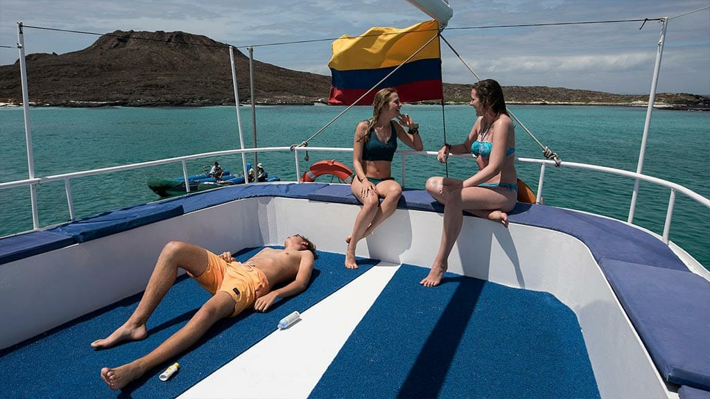 Golondrina yacht Galapagos cruise - tourists sunbathing on top deck