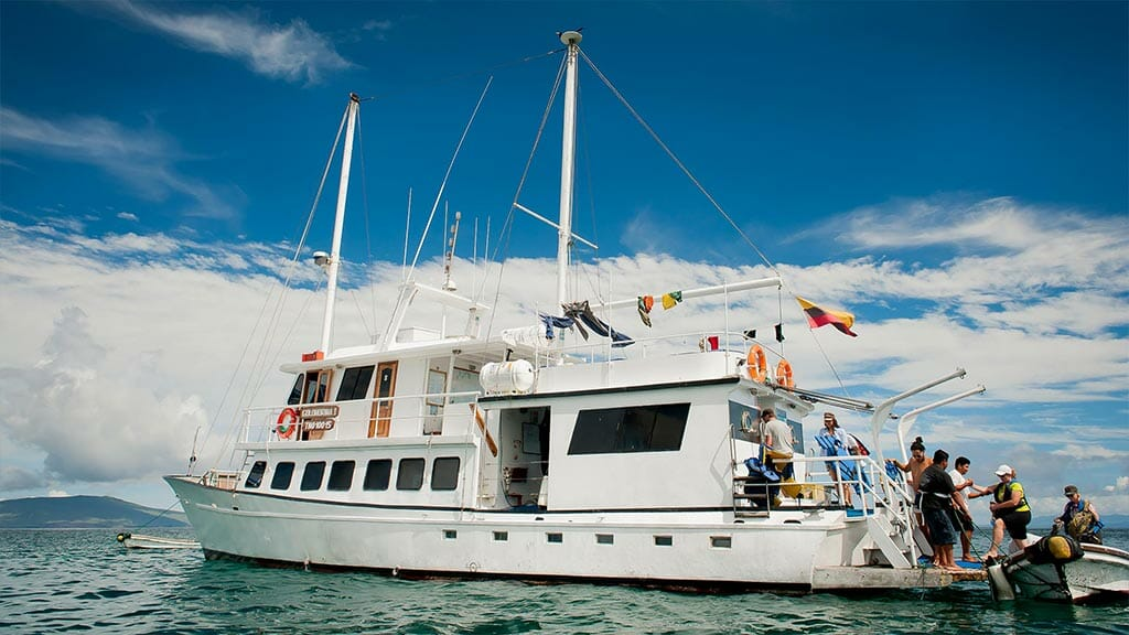 Golondrina yacht Galapagos cruise - side view of yacht as tourists board panga