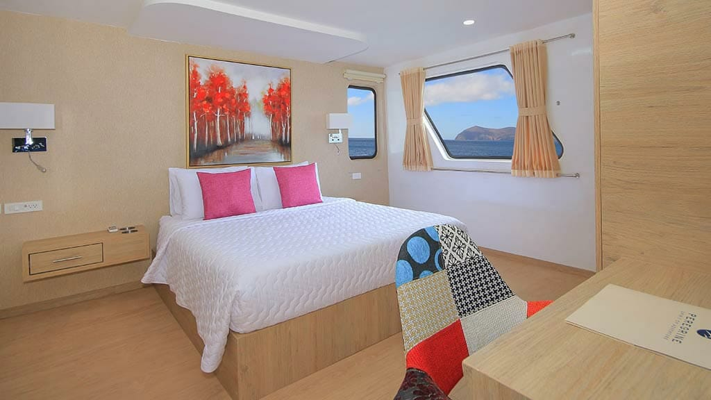double bed guest cabin with large window aboard the Grand queen beatriz yacht at Galapagos islands