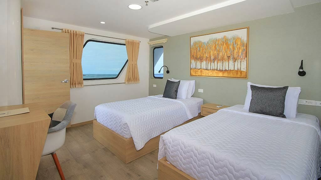 twin guest cabin with wooden flooring and large windows aboard the Grand queen beatriz yacht