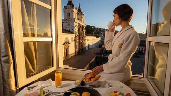 tourist enjoys breakfast on the balcony at casa gangotena hotel quito