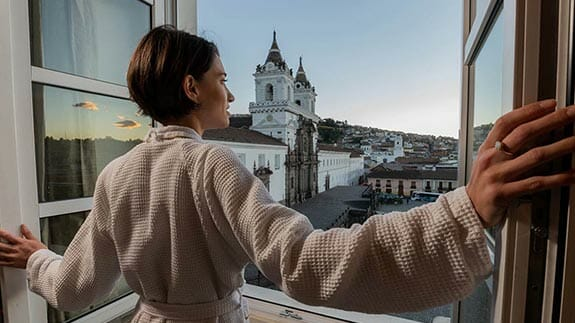 tourist looks out over quito's san francisco plaza from her room balcony at casa gangotena hotel