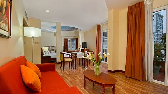 city plaza hotel guayaquil - large suite bedroom with lounge area