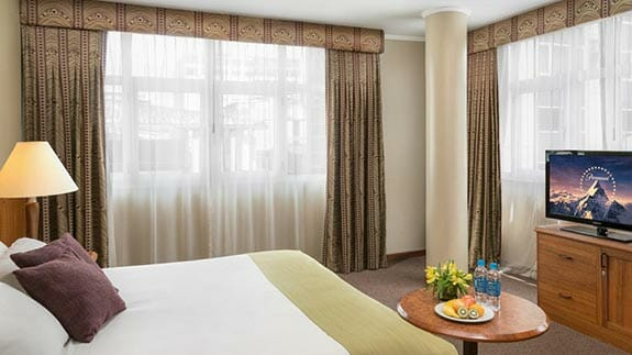 double bedroom with king bed and tv at palace hotel guayaquil ecuador