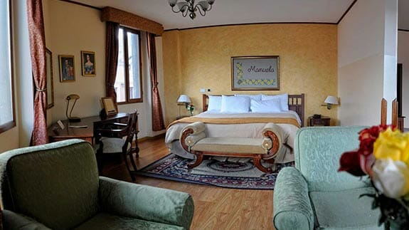double bedroom with lounge area at hotel real audiencia quito